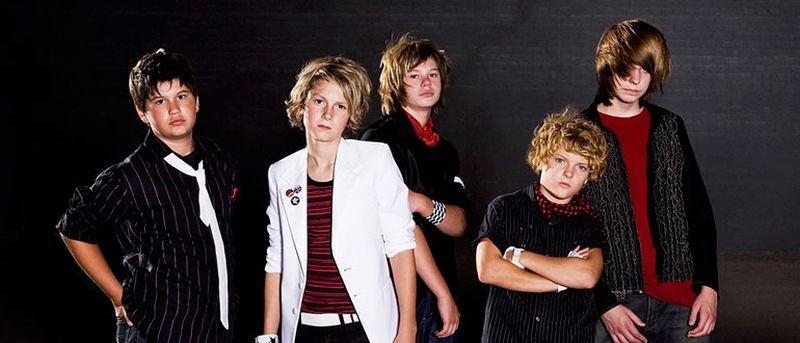 Un grupo de jovencitos con ropa elegante miran a la cámara