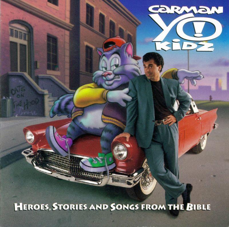 Gran muñeco sentado en un auto rojo el cual abraza una persona que está a su lado con cariño y dicen que son canciones e historias de la biblia