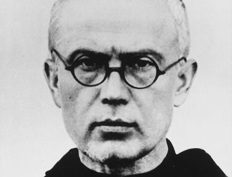 Un sacerdote con gafas mira hacia el frente mientras le toman una foto en primer plano