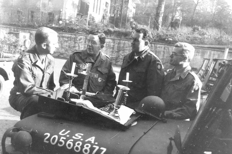 Cuatro capellanes militares charlando sobre un Jeep Willys