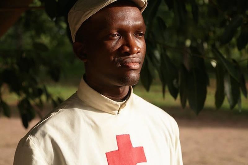Un sacerdote vestido con un traje que lleva el símbolo de la Cruz Roja en su pecho