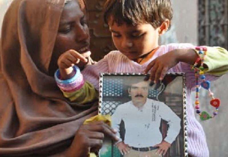 Una mujer musulmana con su hoja pequeña al lado sostienen la foto de su esposo