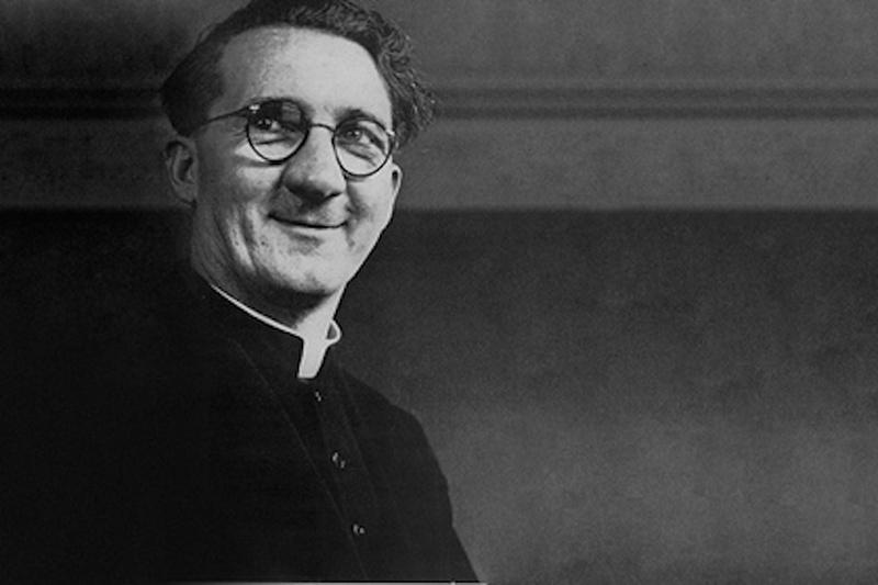 Un sacerdote mayor de edad sonríe hacia el  frente