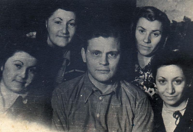 Cuatro mujeres y un hombre en el centro miran hacia la cámara mientras les toman una foto.