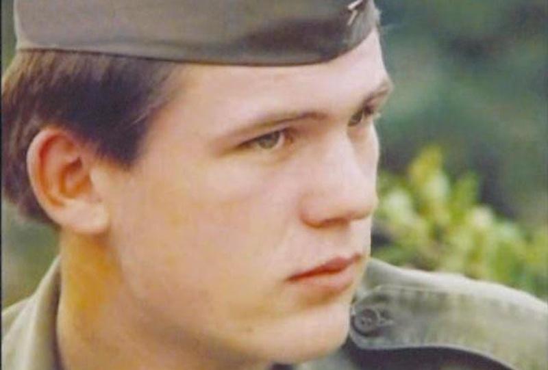 Un joven en vestido militar mira hacia un lado con tan solo su cabeza siendo visible