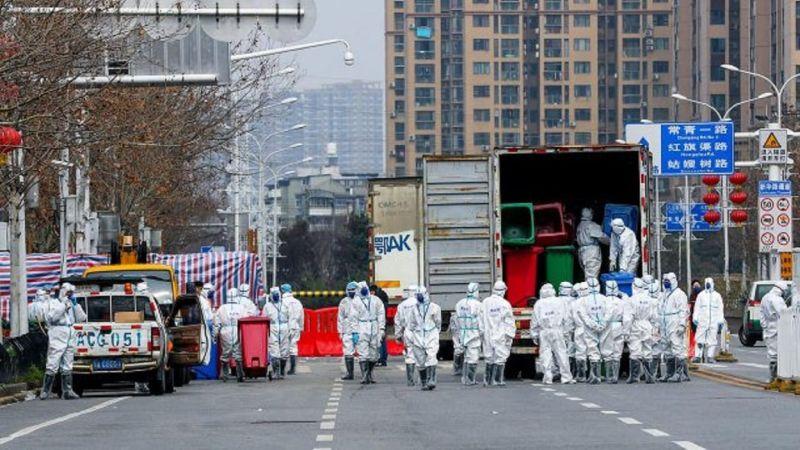 Personas con trajes protectores al lado de un camión
