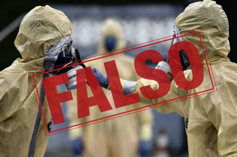 Un hombre limpiando a otro el traje protector y un aviso que dice FALSO
