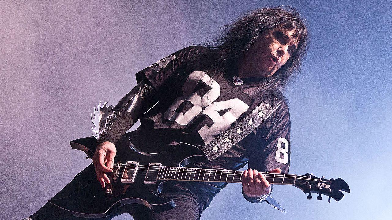 Un guitarrista vestido de negro pelo largo que interpreta su instrumento