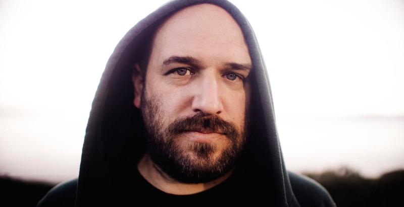 Un señor barbado con un manto sobre su cabeza mira hacia la cámara en un primer plano