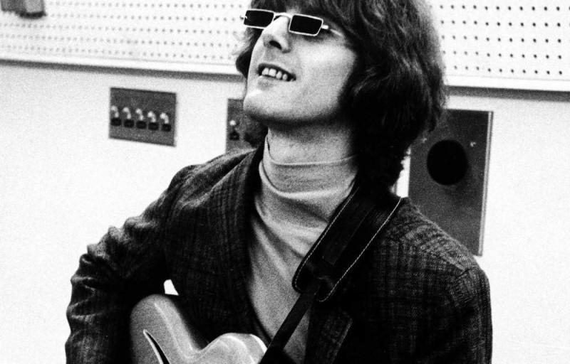 Un músico con guitarra y lentes negros mira hacia arriba en un estudio