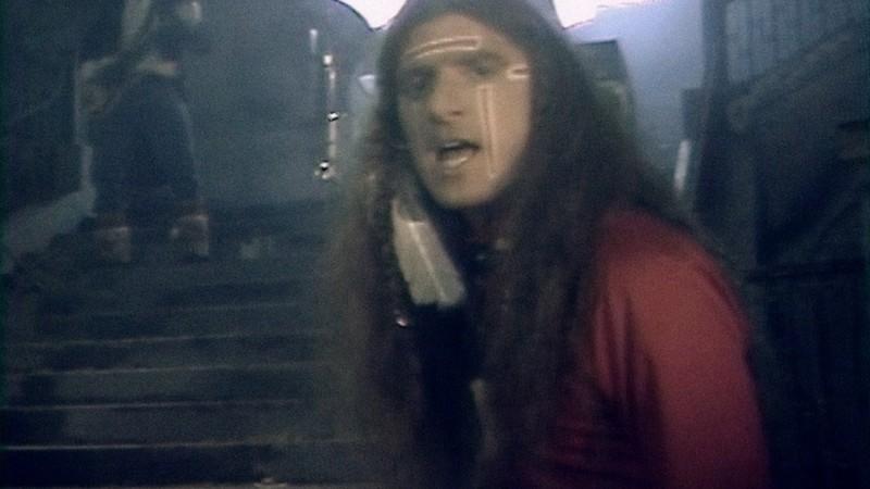 Una escena de un video musical en la que un músico de pelo largo mira a la pantalla con un bajista al fondo