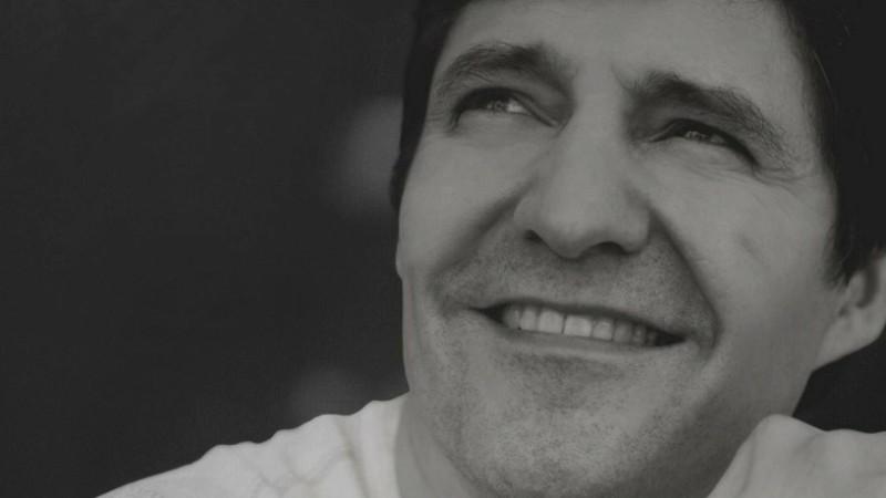 La cabeza de un músico en primer plano mientras mira sonriente hacia arriba