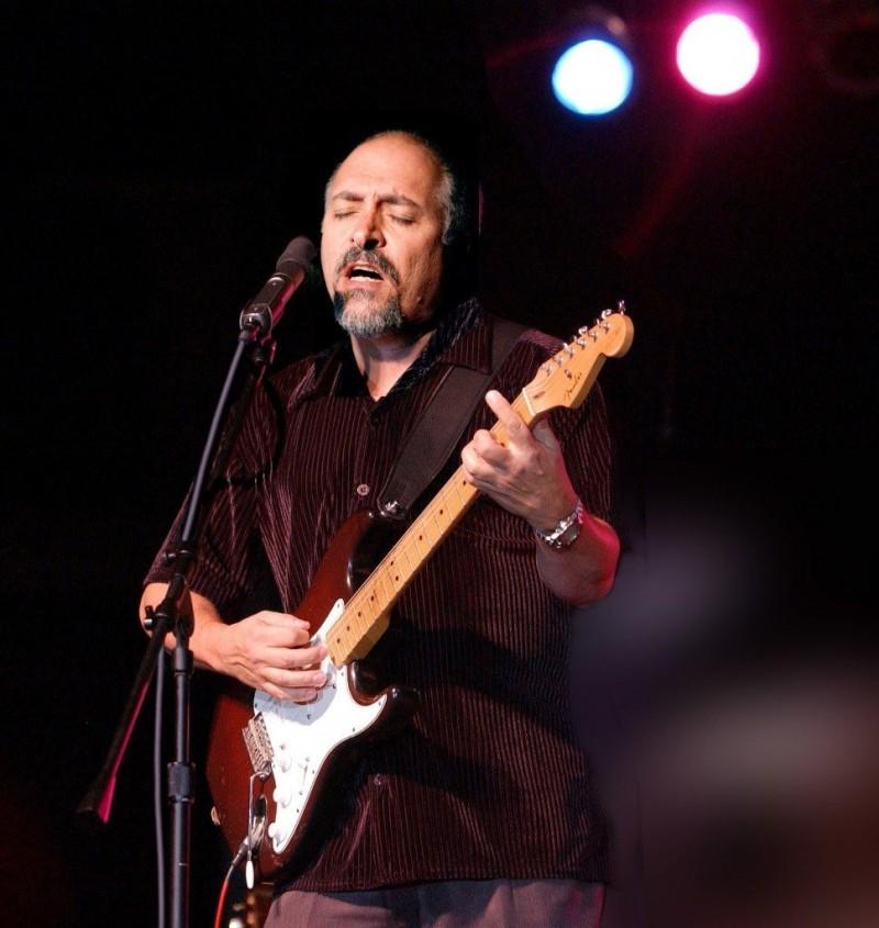 Un músico en un concierto toca su guitarra apasionadamente