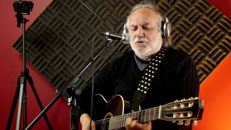 Un músico toca su guitarra y canta a la vez en un estudio de grabación