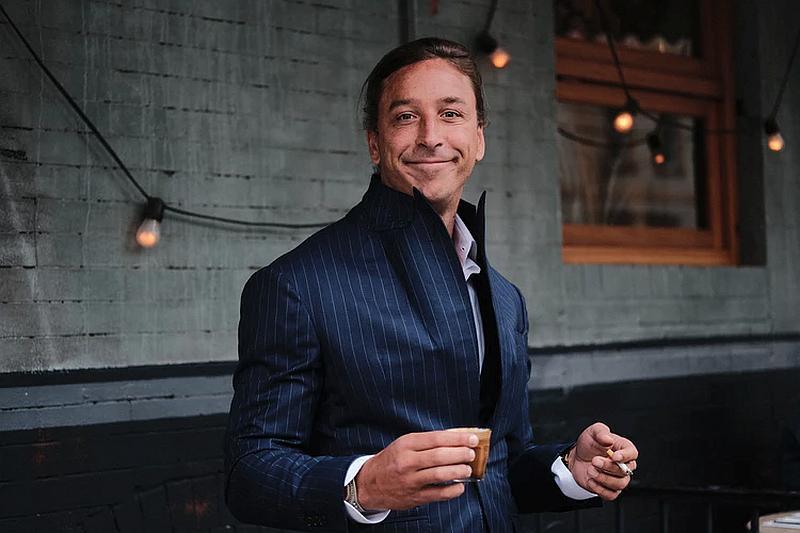 tenemos un hombre que sonríe y tiene un pocillo en su mano con un traje elegante gante