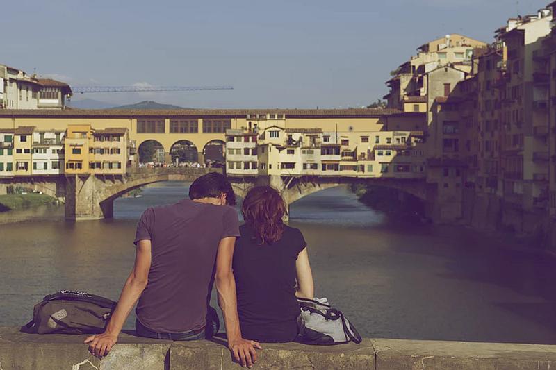 Una pareja que observa una ciudad  un puente y el mar