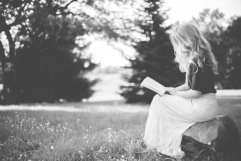 Una mujer joven en medio de la naturaleza  lee un libro muy tranquila