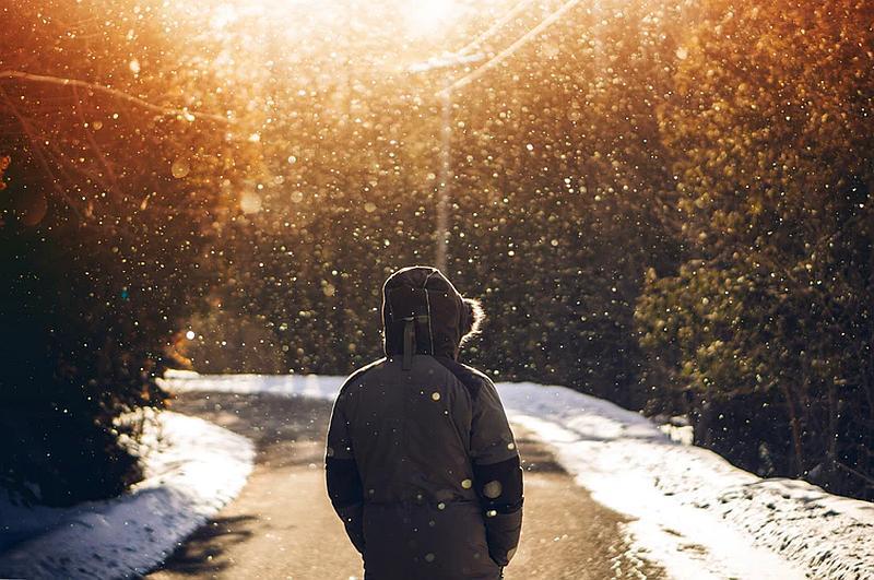 Vemos auna persona con chaqueta y capucha en un atardecer de otoño cayendo una suave nevada