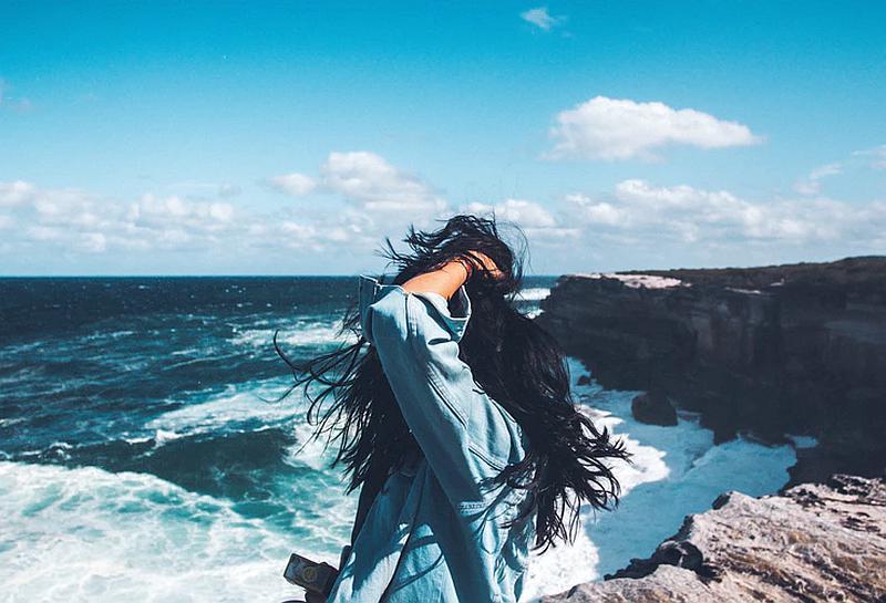 Vemos una mujer  con su pelo revuelto por la brisacomtemplando el mar