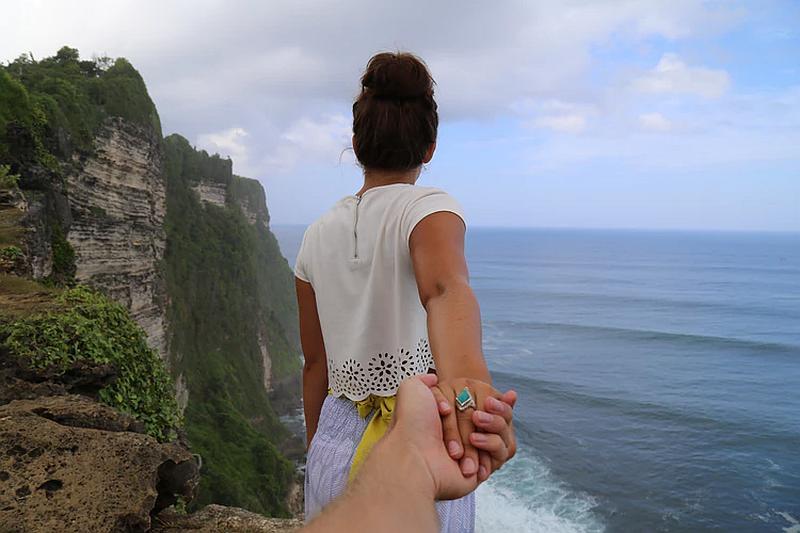 vemos una mujer  de espaldas tomada de la mano contemplando el mar