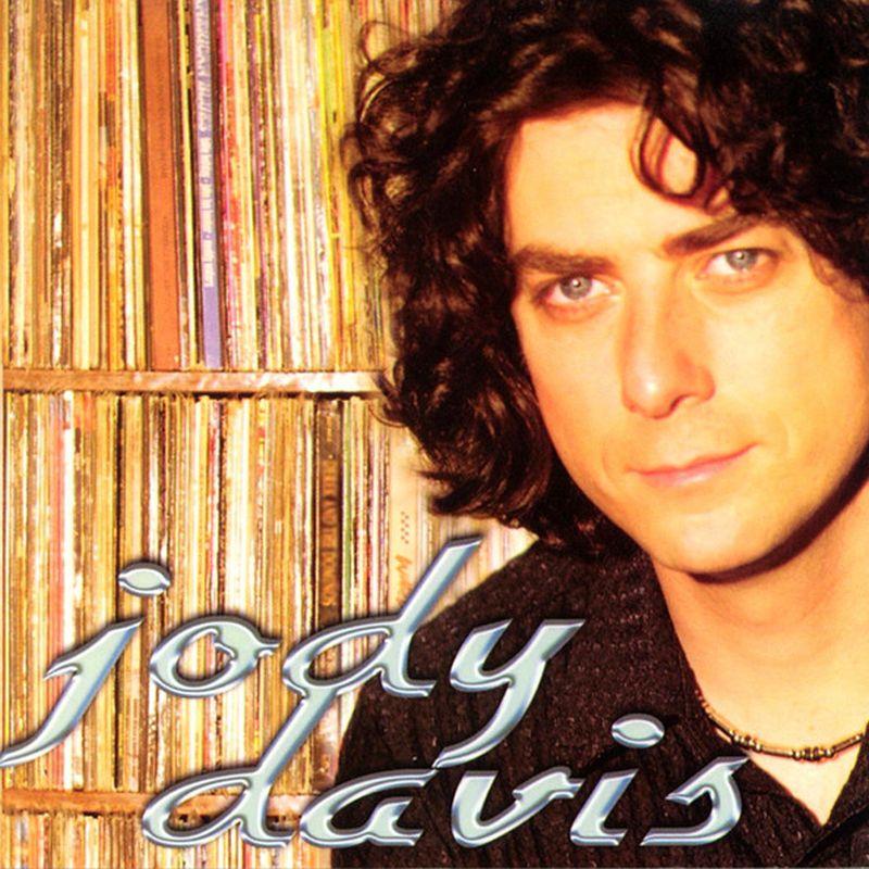 Un hombre con rostro agradable ojos verdes y pelo crespo y una media sonrisa y un nombre Jody davis