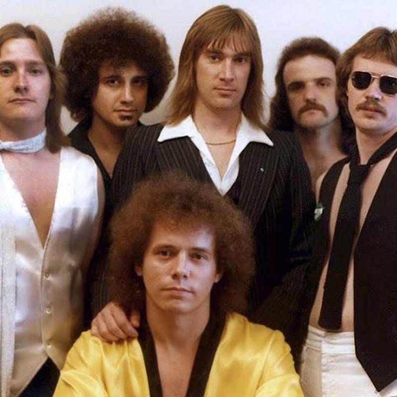 Un grupo de rock con 6 integrantes posando amablemente
