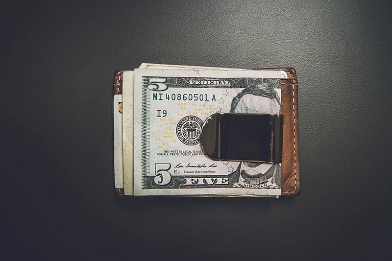 Vemos una billetera y encima un fajo de billetes de cinco dolares