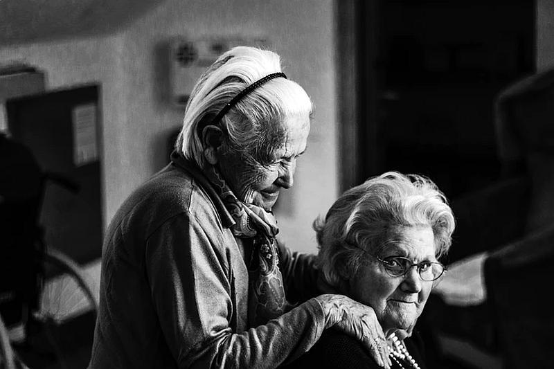 Vemos ados personas muy mayores donde una coloca sus brazos en los hombros de la otra