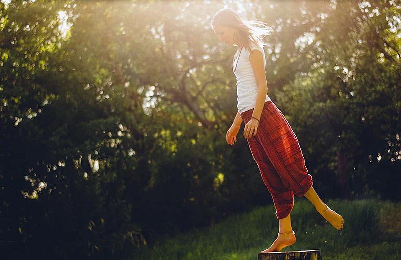 Vemos una mujer  descalza que  levanta un solo pie sobre un tronco de árbol cortado en un claro de un bosque