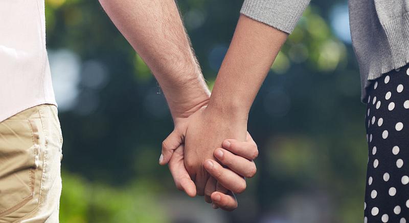 Vemos las manos entrelazadas de una pareja que camina  tranquila
