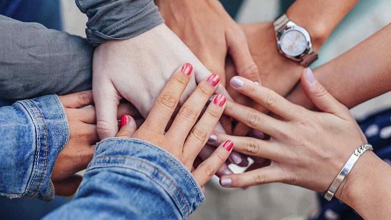 Vemos varias manos de hombres y mujeres unas encimas de otras que descansan
