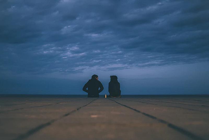Una pareja conversando en una tarde con nubes muy espesas
