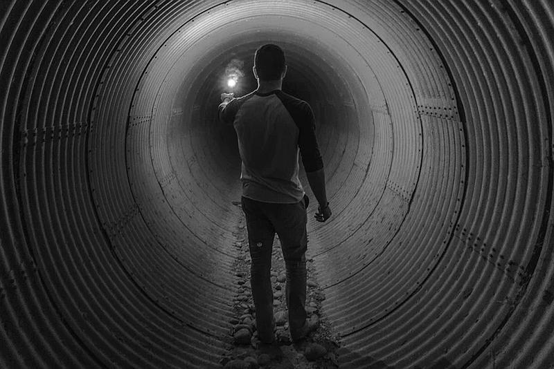 Vemos aun hombre joven en la entrada de un túnel