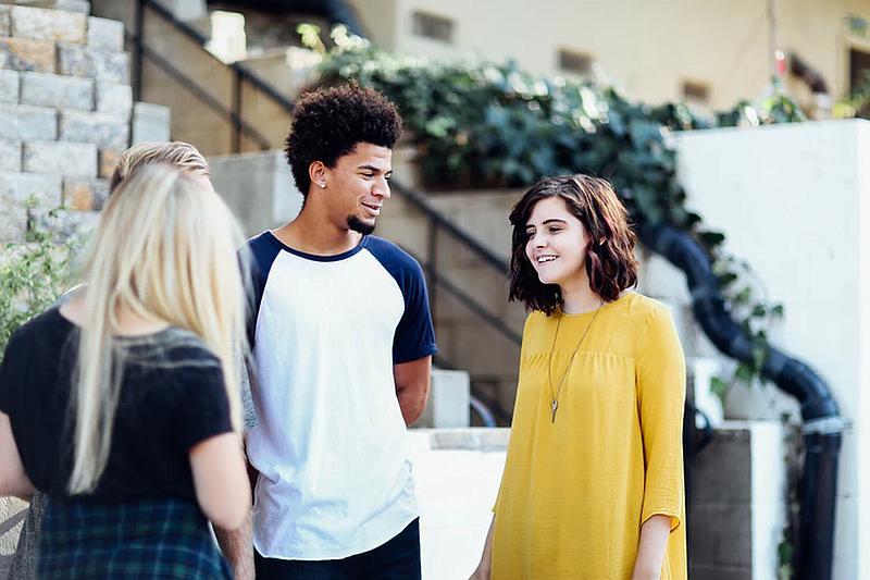 Vemos a un joven que habla con dos jóvenes mujeres una de espaldas y la otra que le sonrie