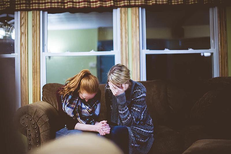 Vemos a dos mujeres  tomadas de la manos y sus rostros  cabizbajos están en oración