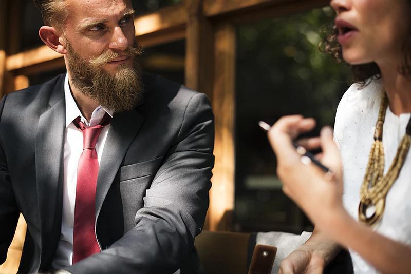 Vemos a una pareja que dialoga el con barba y corbata y ella con collar muy elegante