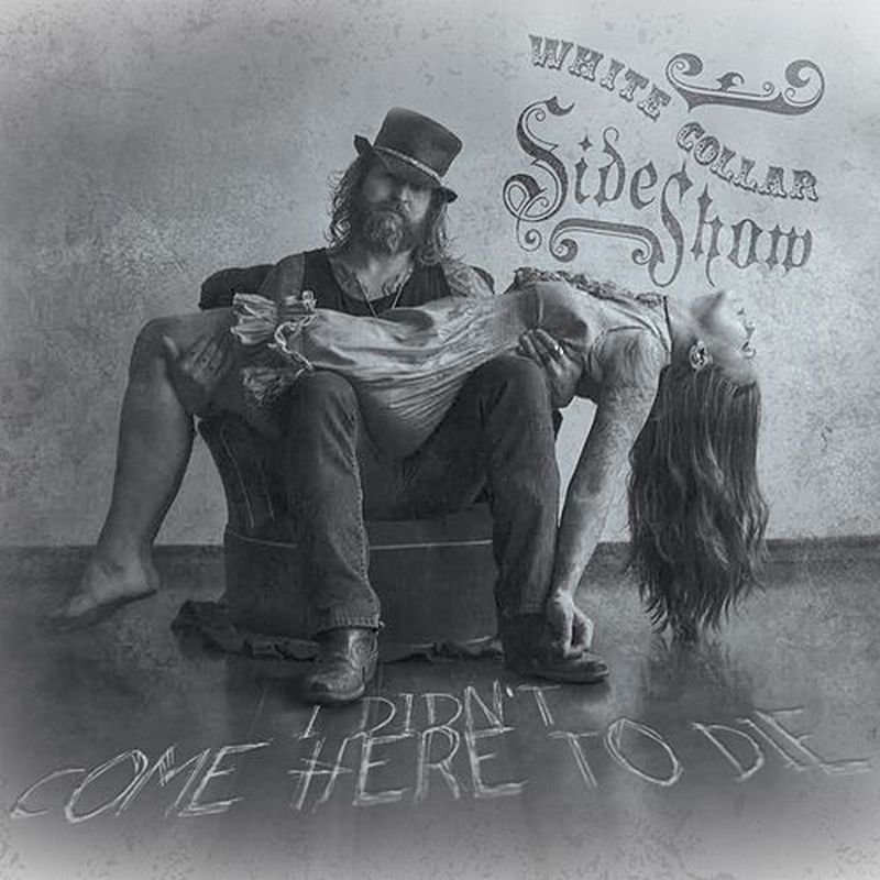 Un hombre sentado con pelo largo y barba que sostiene una mujer en brazos se lee  no quiero venir aquí para morir