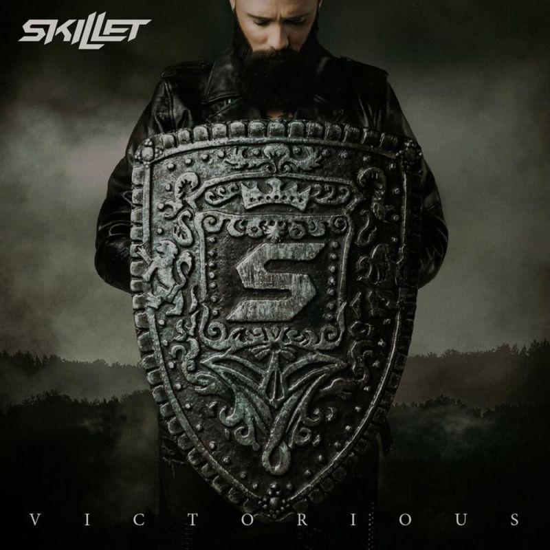 Un hombre con su cara agachada y tiene un escudo grabado con la palabra victoria
