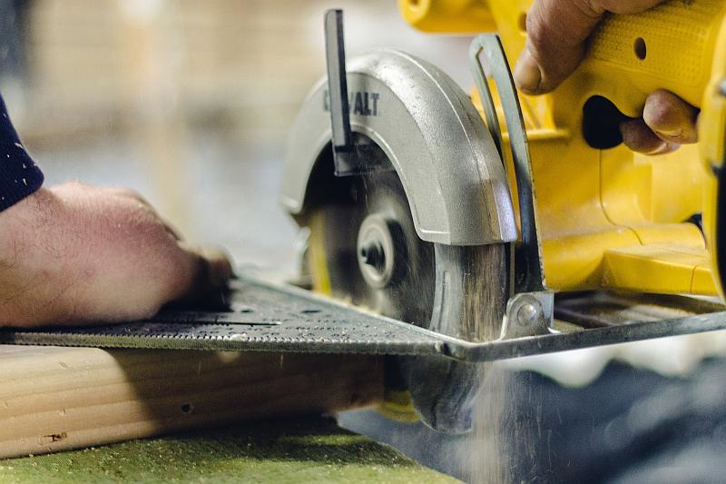Vemos auna persona que maneja una maquina cortadora de color amarillo
