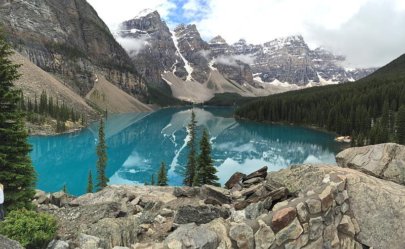 Vemos un hermoso paisaje con un lago montañas con nieve y bosques de pinos