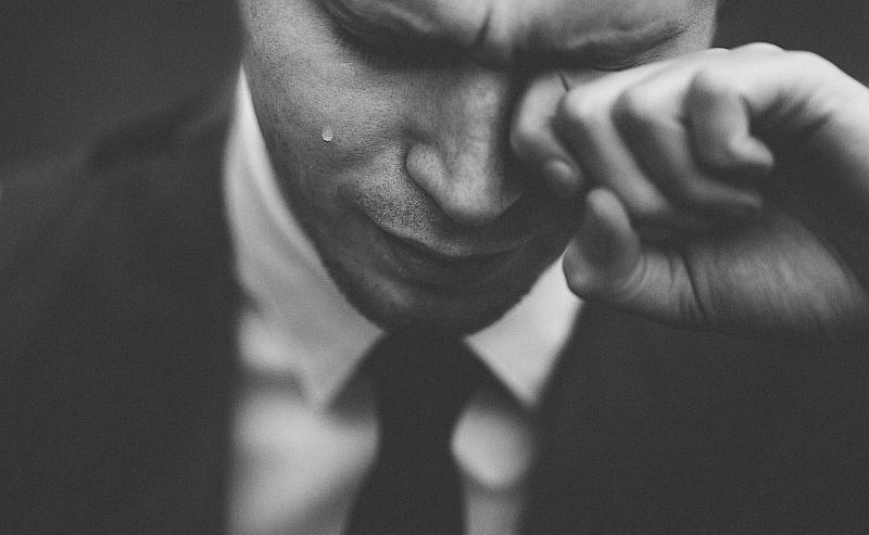 Vemos un hombre con corbata  que llora y limpia sus lagrimas