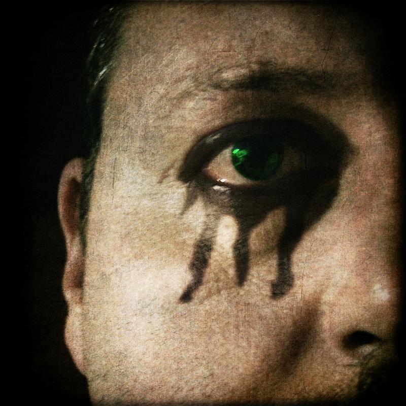 Vemos un rostro de hombre con un ojo verde tono metálico y abajo pintadas unas pestañas grandisimas