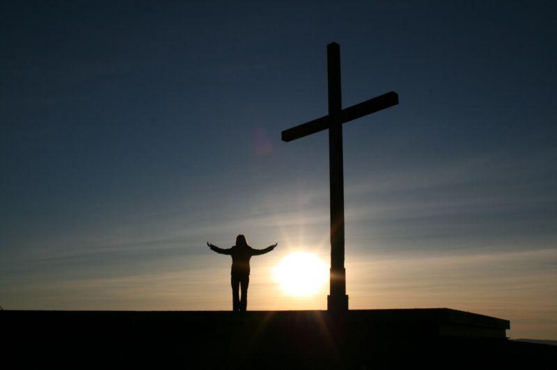 Vemos un lindo atardecer una cruz y una persona que levanta sus manos