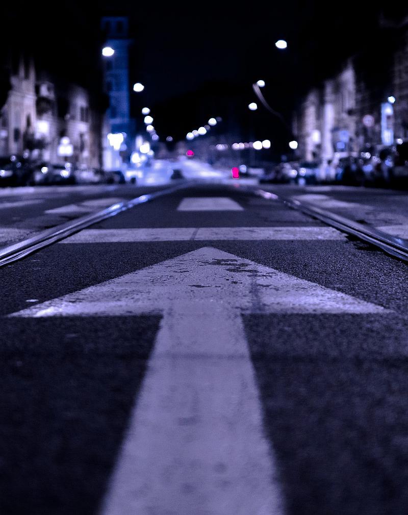 Vemos una avenida en una ciudad grande donde el piso esta señalizado con flechas