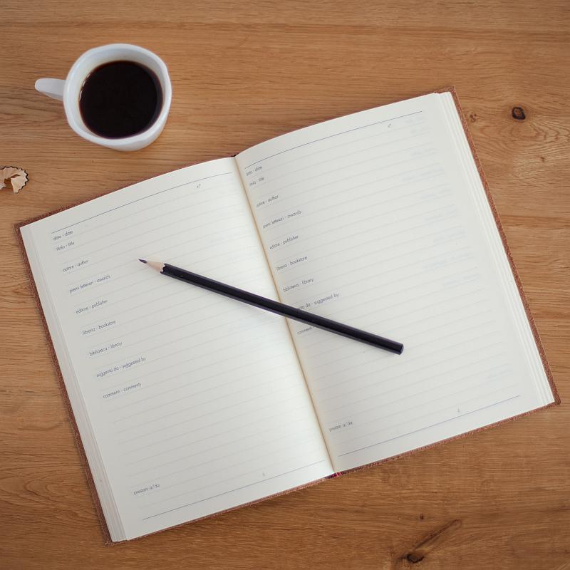 Vemos una agenda abierta con un lápiz encima  y al lado un pocillo de café
