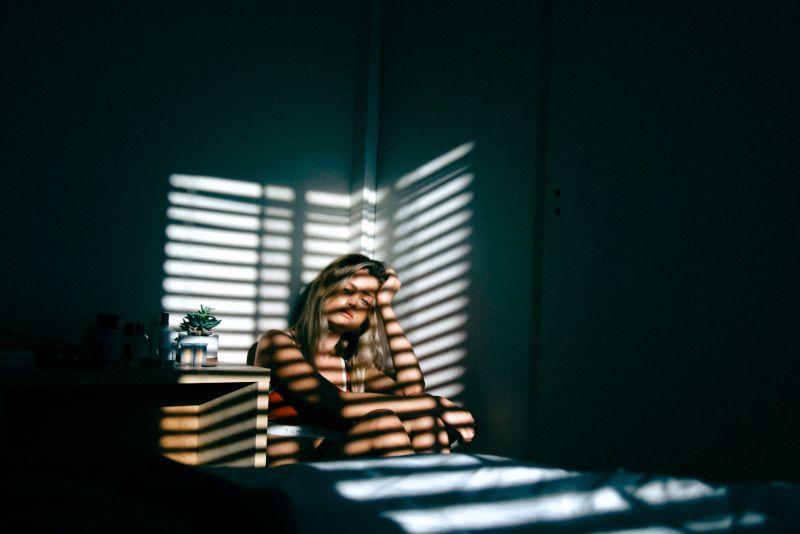 Vemos una mujer rubia entre dormida que entra luz a través de una persiana