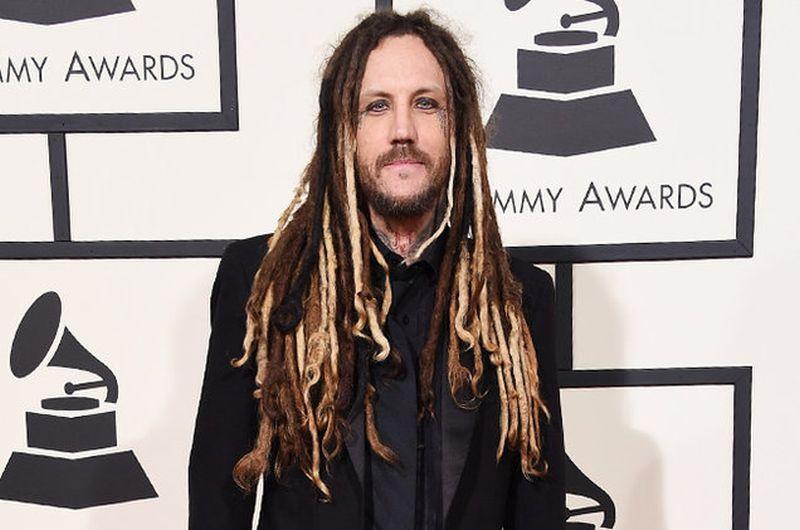 Hombre de pelo largo con rastas, barba  y de traje