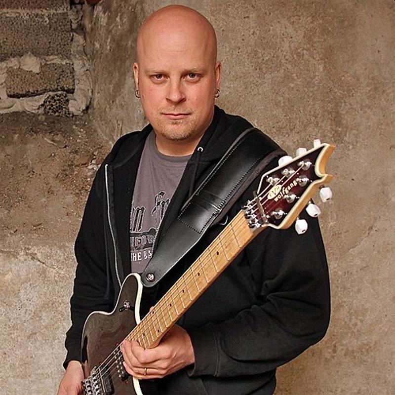 Un hombre calvo con una sonrisa y con una guitarra
