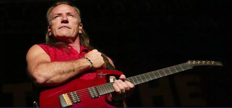 Un hombre rubio con camisa roja sin mangas y tocando su guitarra