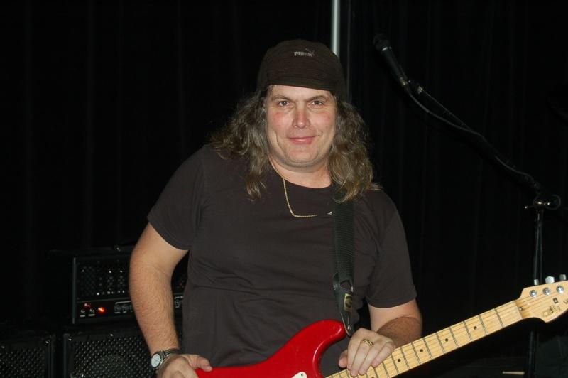 Un músico de pelo largo con su guitarra y sonriendo